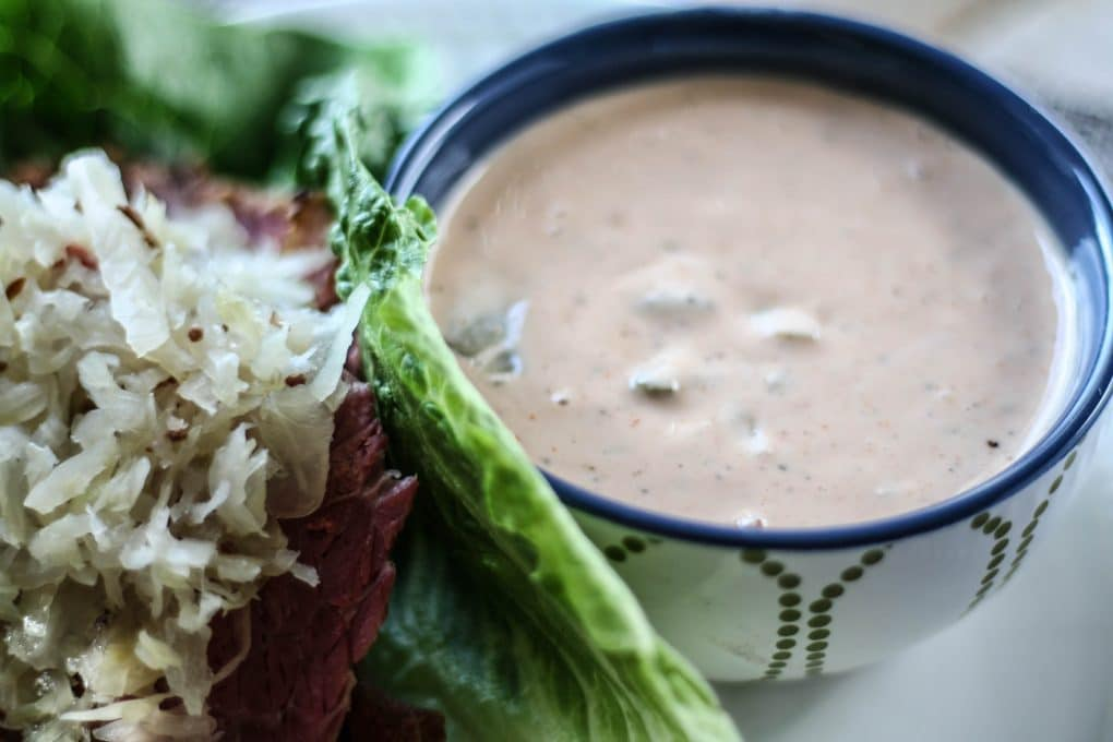 a bowl of paleo thousand island dressing next to a paleo reuben lettuce wrap