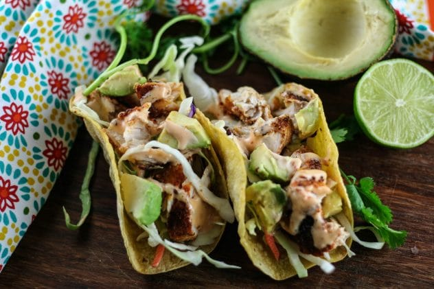 two blackened mahi mahi tacos sitting on a wooden cutting board.