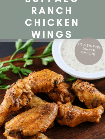 buffalo ranch chicken wings sitting on a wooden cutting board. There is parsley garnishment behind the wings and a bowl of dairy-free ranch dressing sitting nearby.