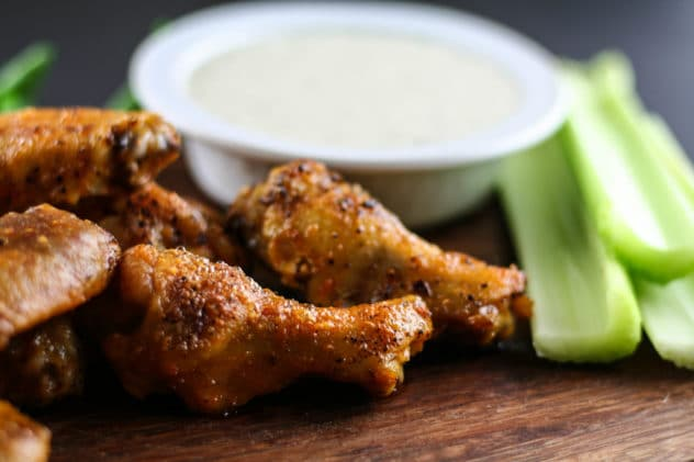 buffalo ranch chicken wings sitting on a wooden cutting board. There is a bowl of dairy-free ranch dressing sitting nearby and cut celery.