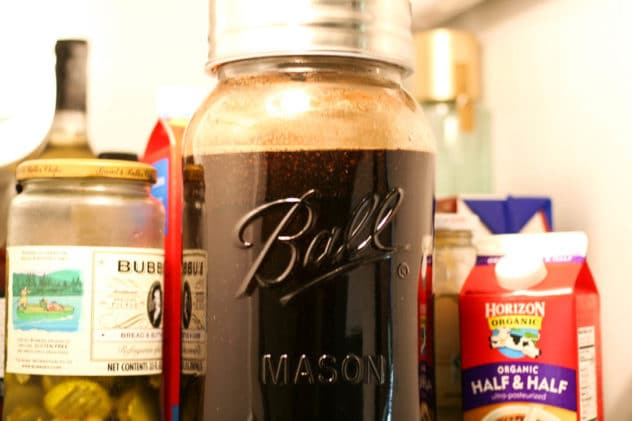 a gallon jug of cold brew coffee inside a refrigerator