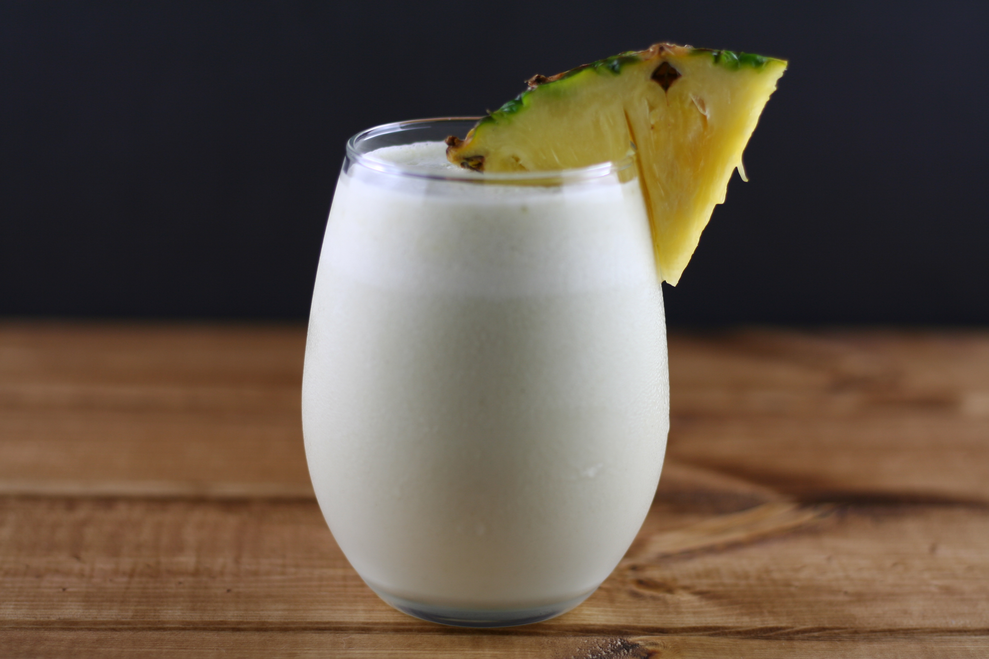 a glass of coconut pineapple matcha smoothie with a chunk of fresh pineapple stuck on the rim of the glass.