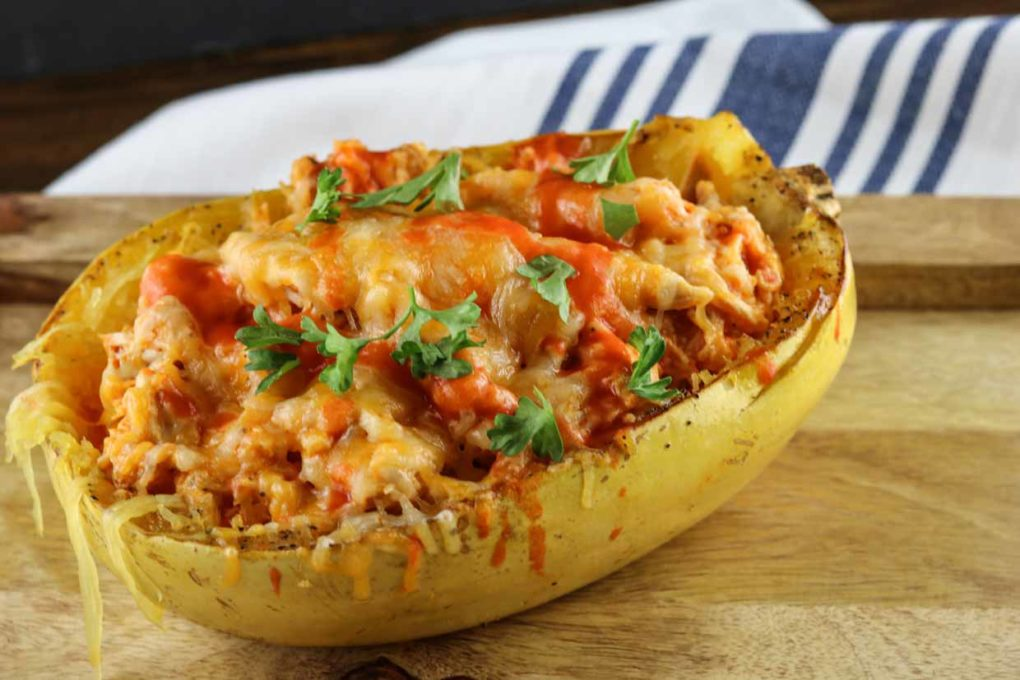 buffalo chicken spaghetti squash on a wooden cutting board