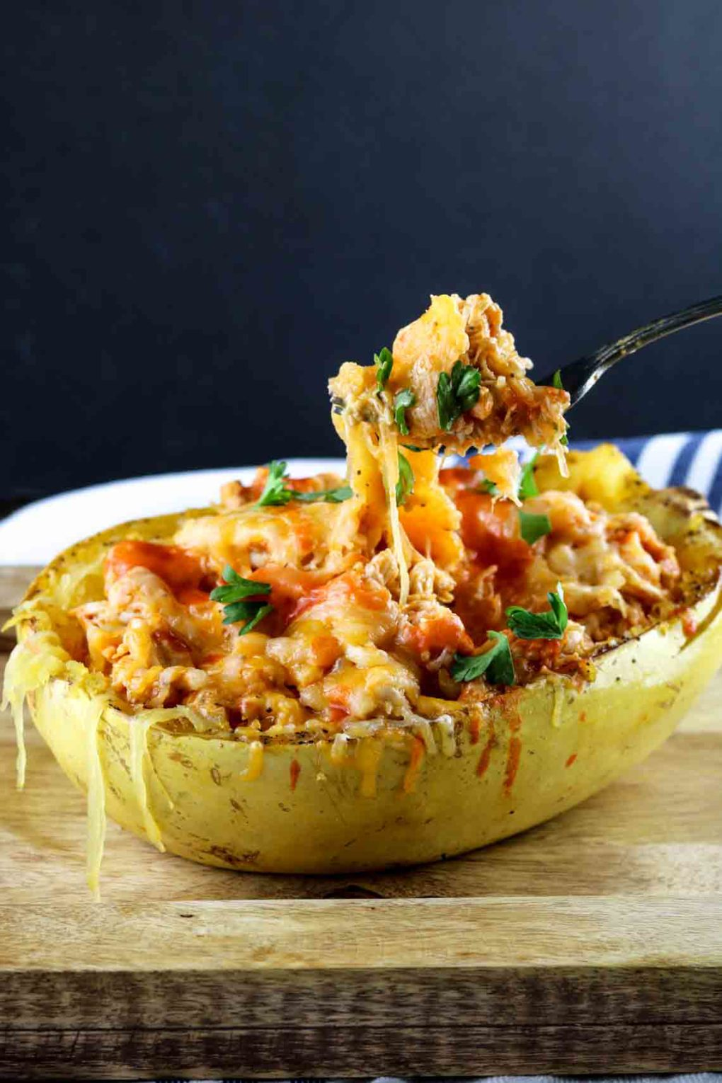 buffalo chicken spaghetti squash with someone pulling up a bite on a fork
