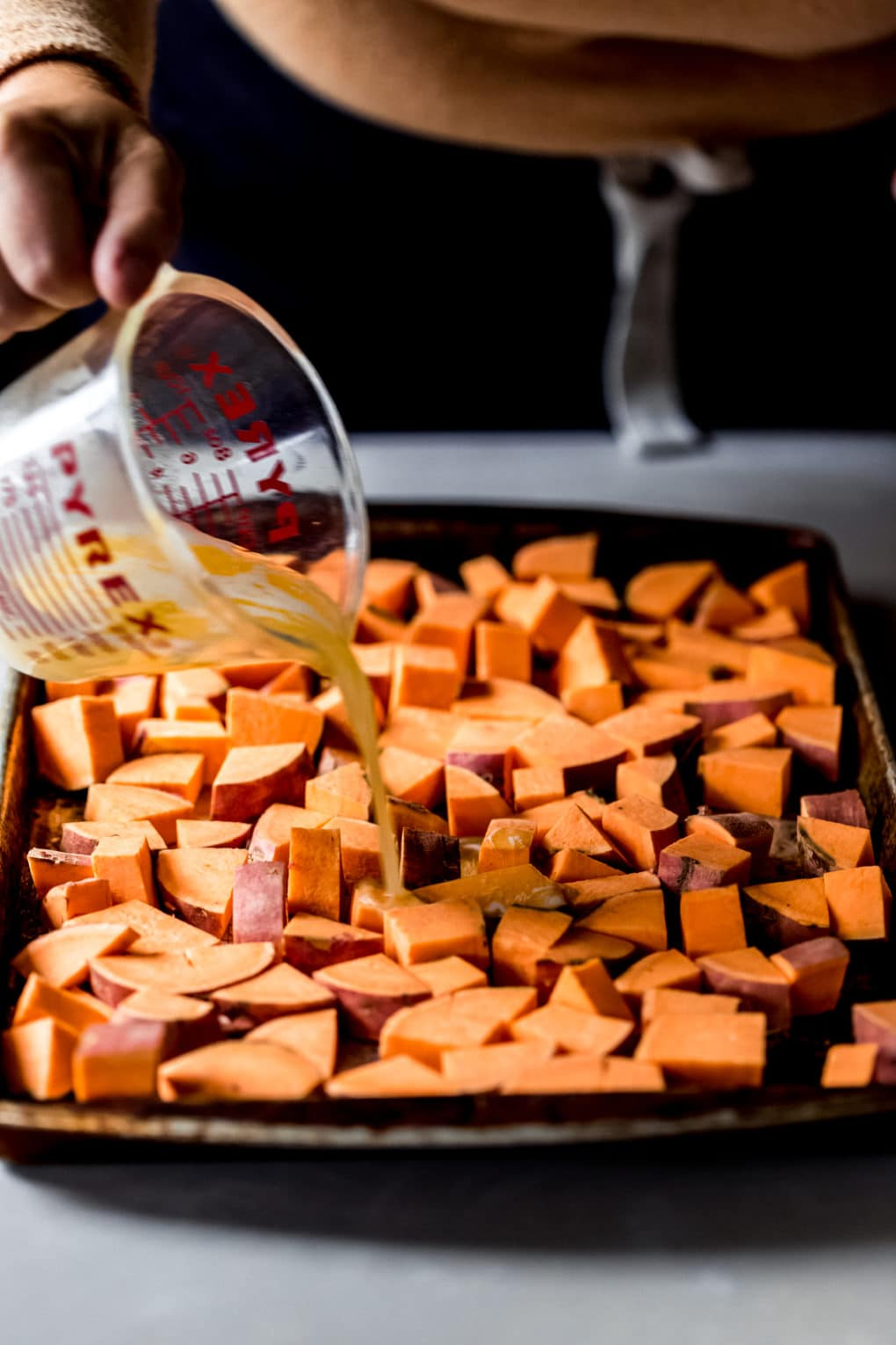 a woman pouring melted butter over a tray of diced sweet potatoes
