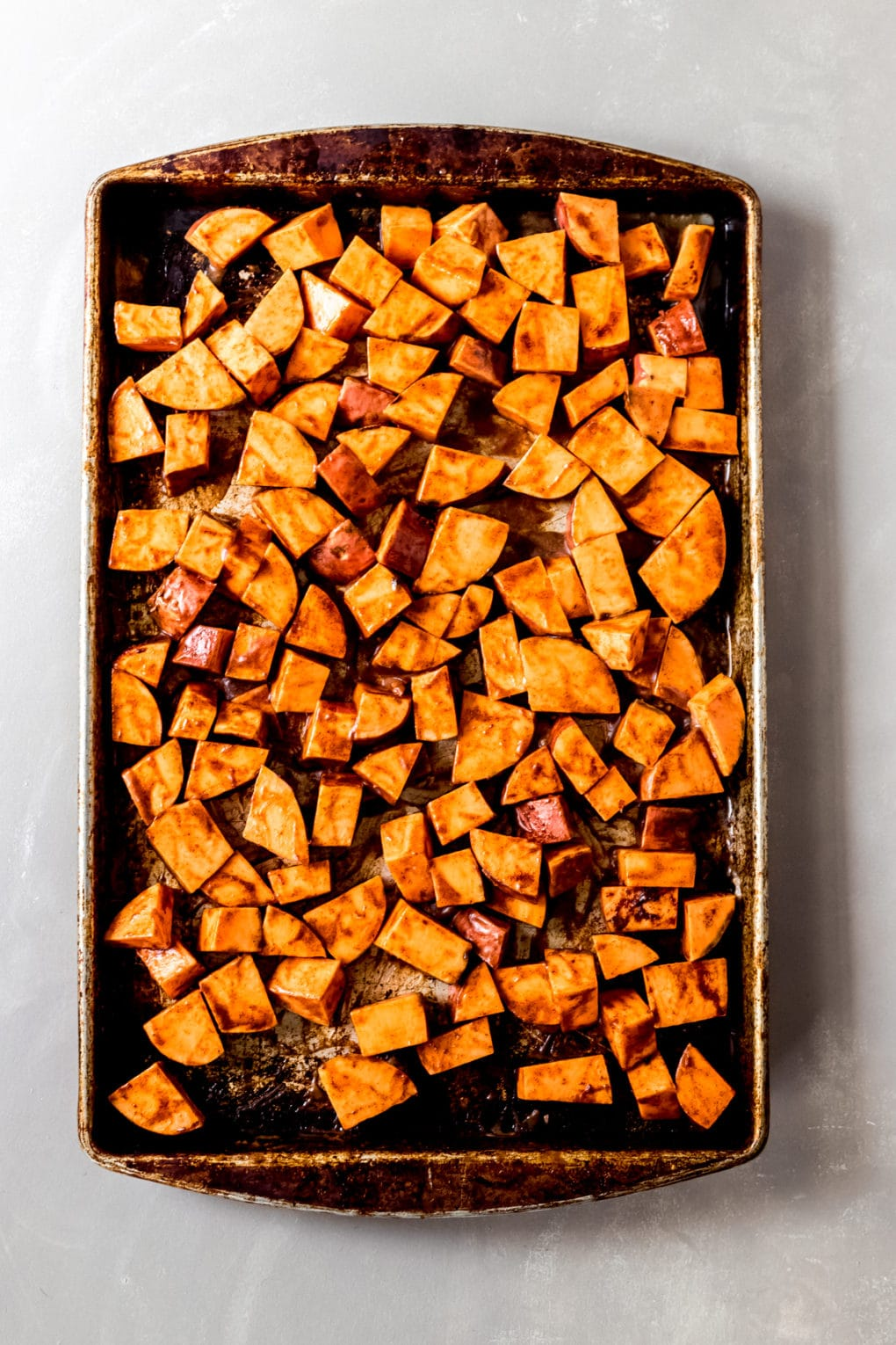 a baking sheet with unbaked cinnamon honey sweet potatoes