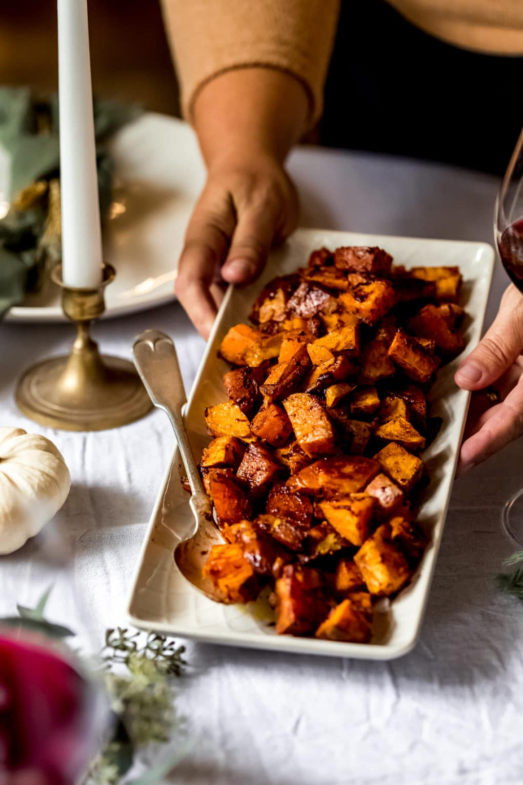 a woman serving a dish of cinnamon honey sweet potatoes onto a thanksgiving table