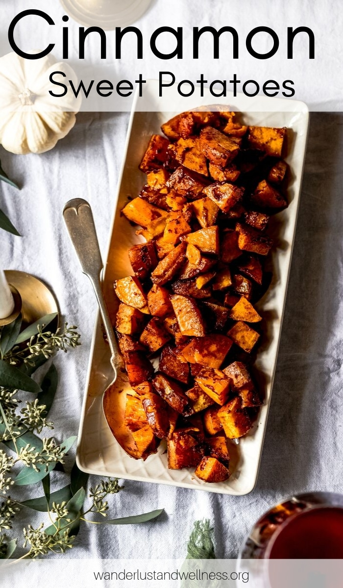 a narrow platter of cinnamon honey sweet potatoes on a thanksgiving table scene