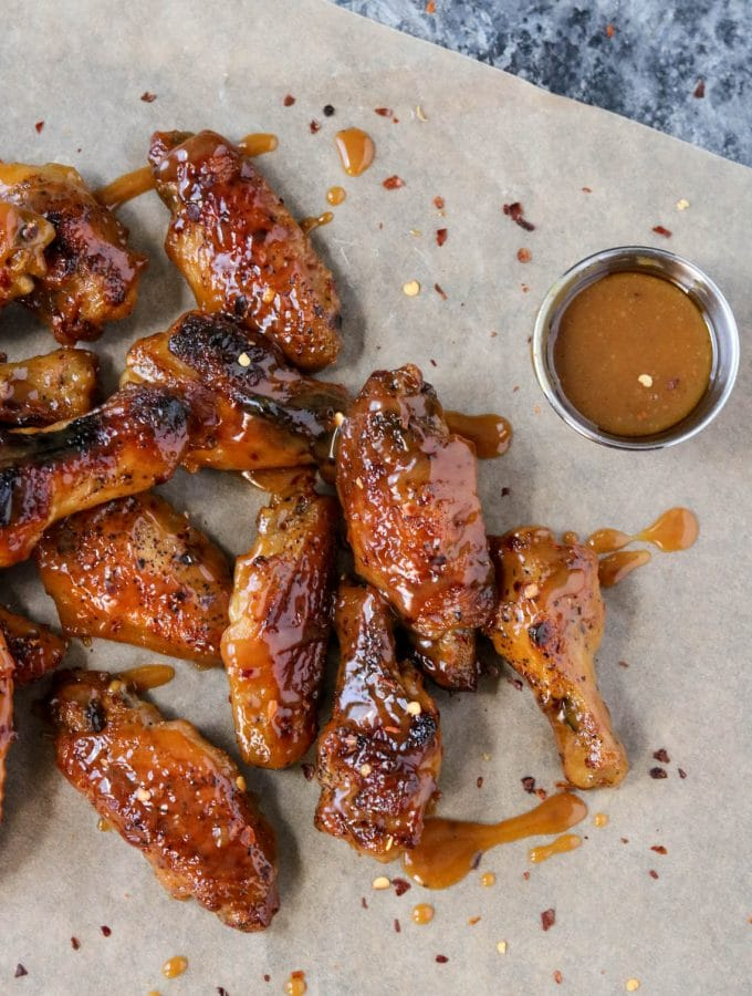 Hot Honey Mustard Wings laying on brown parchment paper with a small cup of hot honey mustard sauce sitting nearby