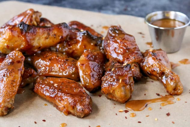 a pile of hot honey mustard wings on brown parchment paper