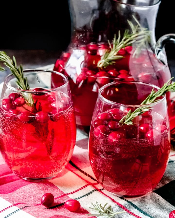 a glass pitcher of Christmas sangria with two glasses filled nearby