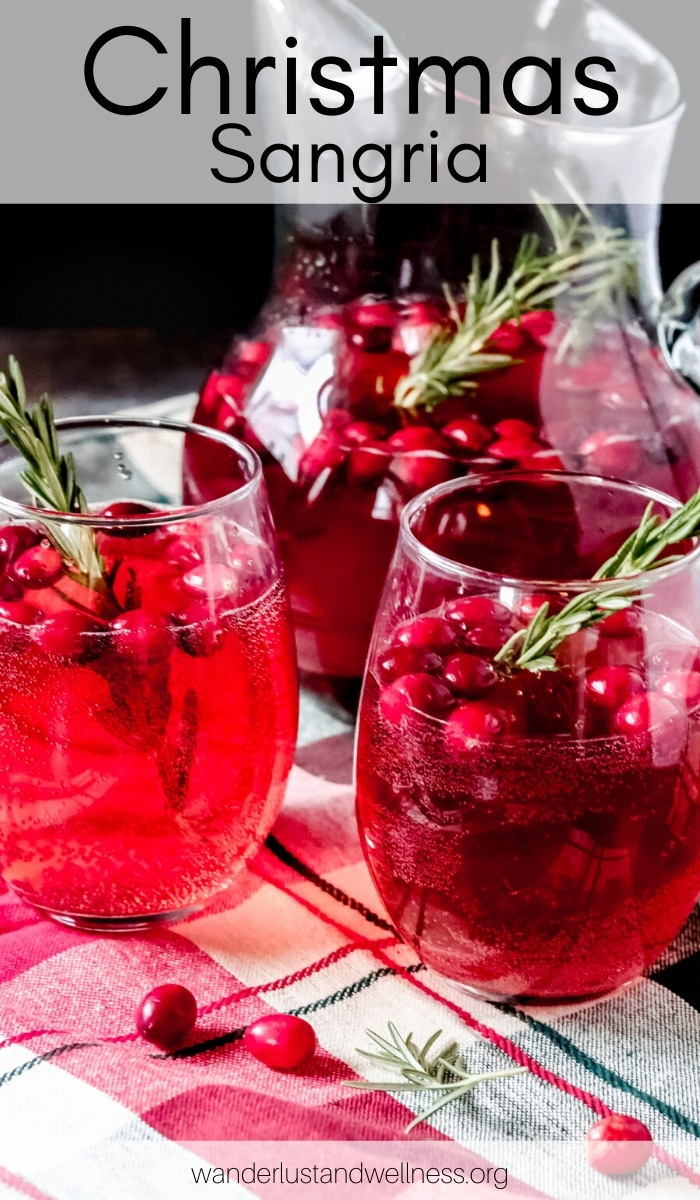 a glass pitcher of Christmas sangria with two glasses sitting beside it