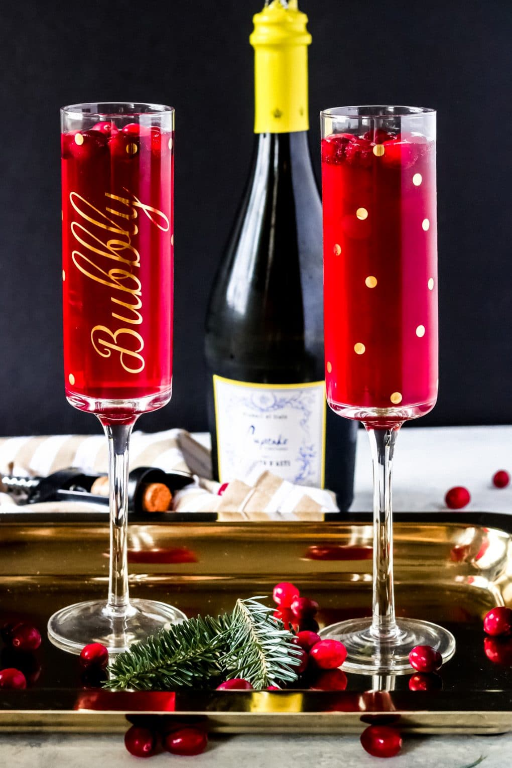 two glasses of cranberry mimosa on a gold serving tray with a bottle of moscato d'asti in the backgrounders