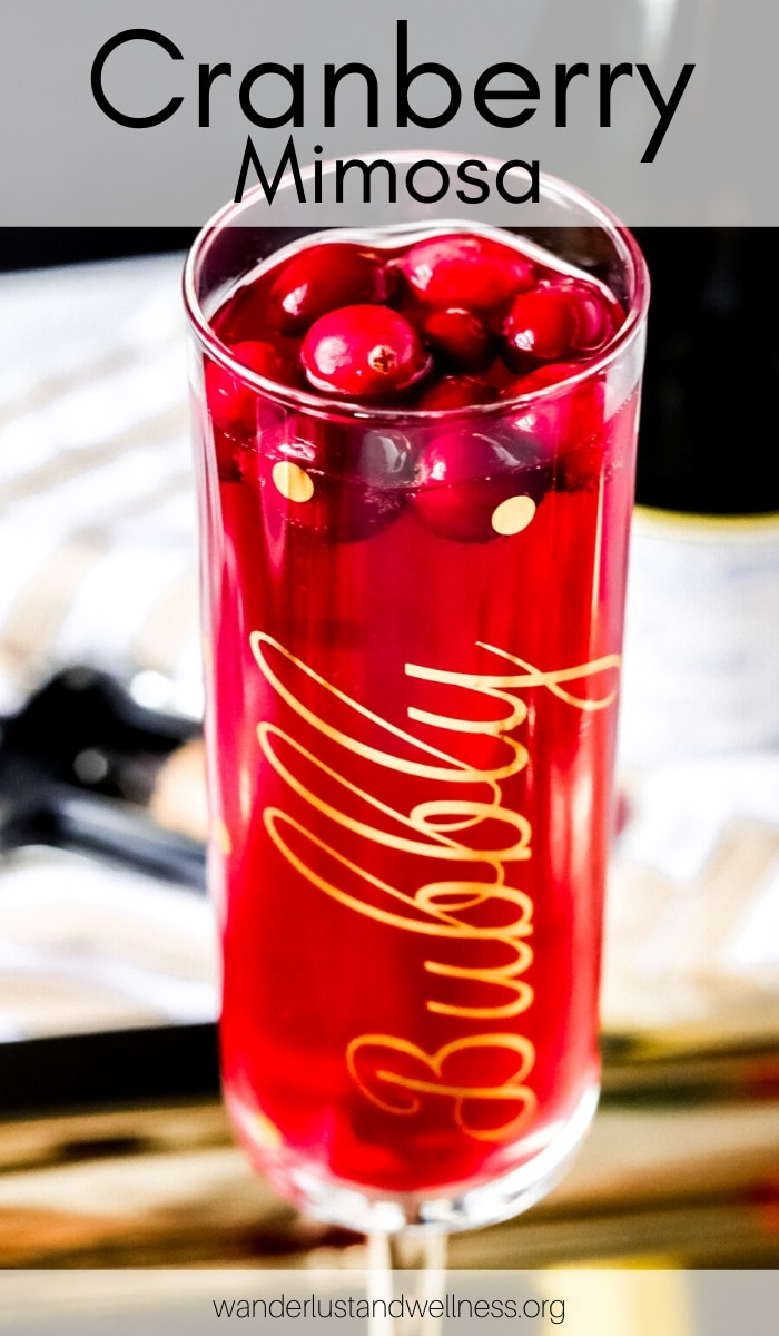 a glass of cranberry mimosa on a gold serving tray