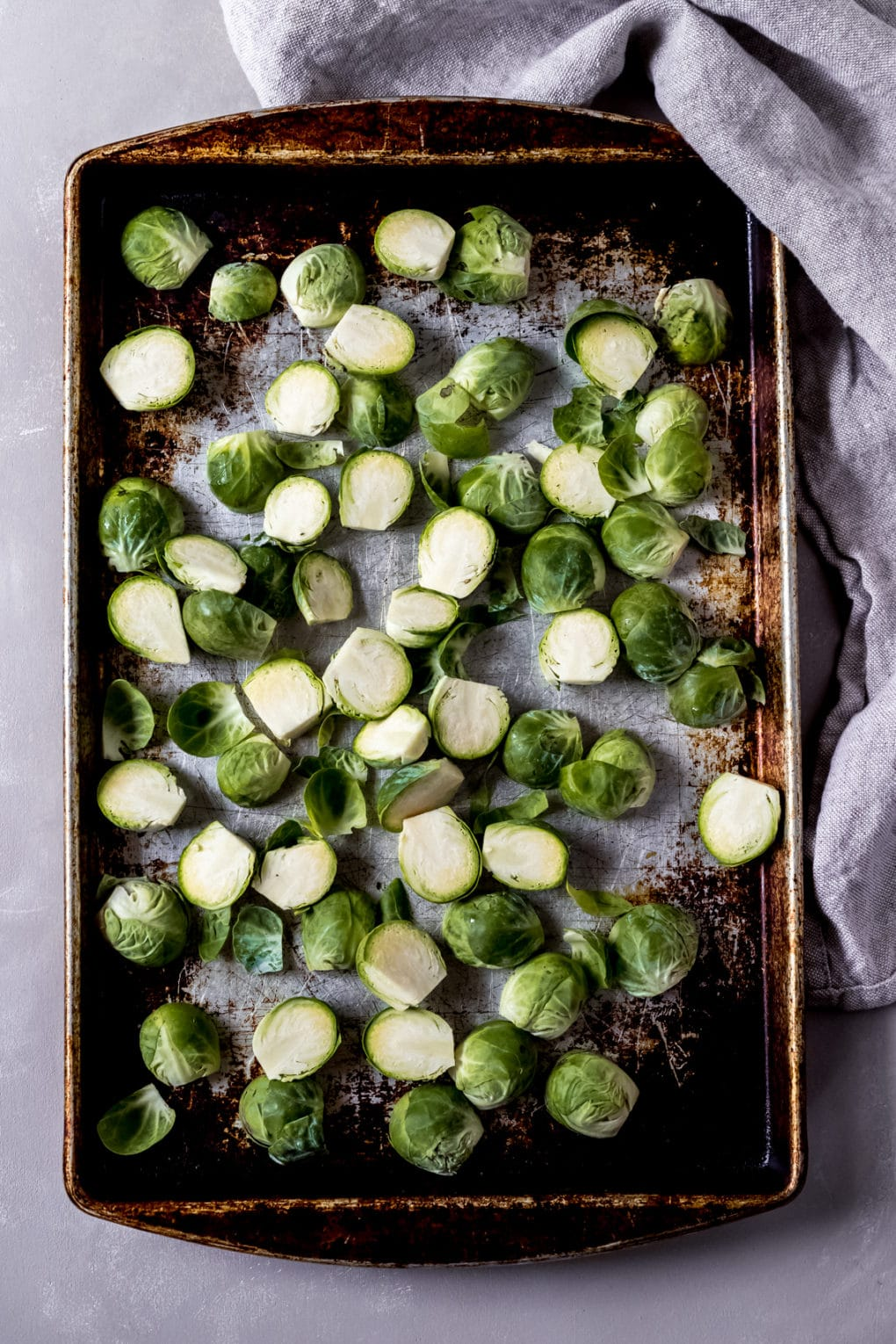a baking sheet with raw brussel sprouts