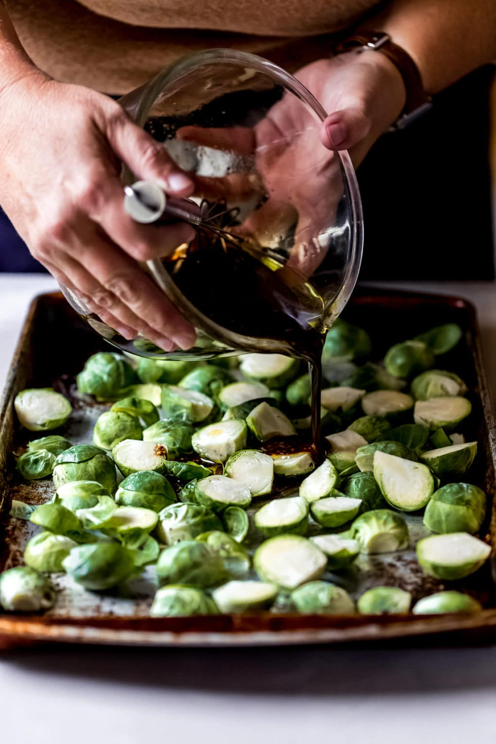 a woman pouring over the glaze for caramelized brussel sprouts
