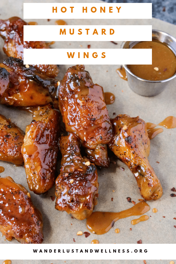 a close up shot of hot honey mustard wings with a sauce container of hot honey mustard sauce sitting next to them