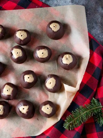 several sunbutter buckeyes on a sheet of parchment paper on top of buffalo plaid material