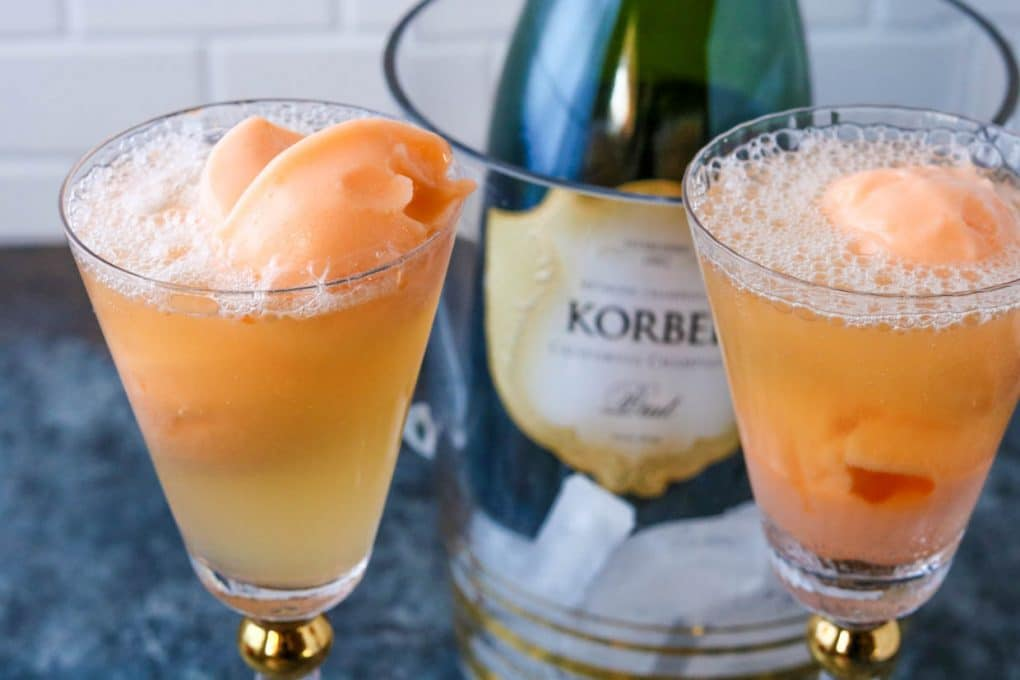 two glasses of orange sherbet champagne floats with a bottle of champagne in the background