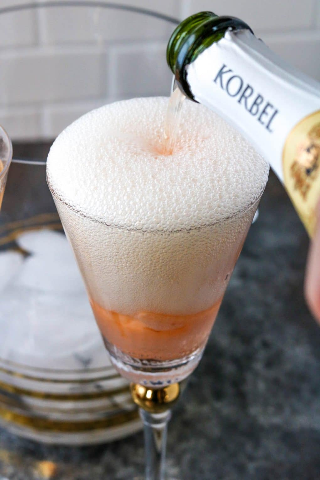 champagne being poured over orange sherbet in a glass