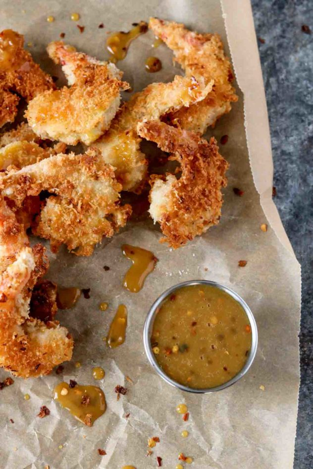 a pile of coconut shrimp with a spicy honey mustard sauce