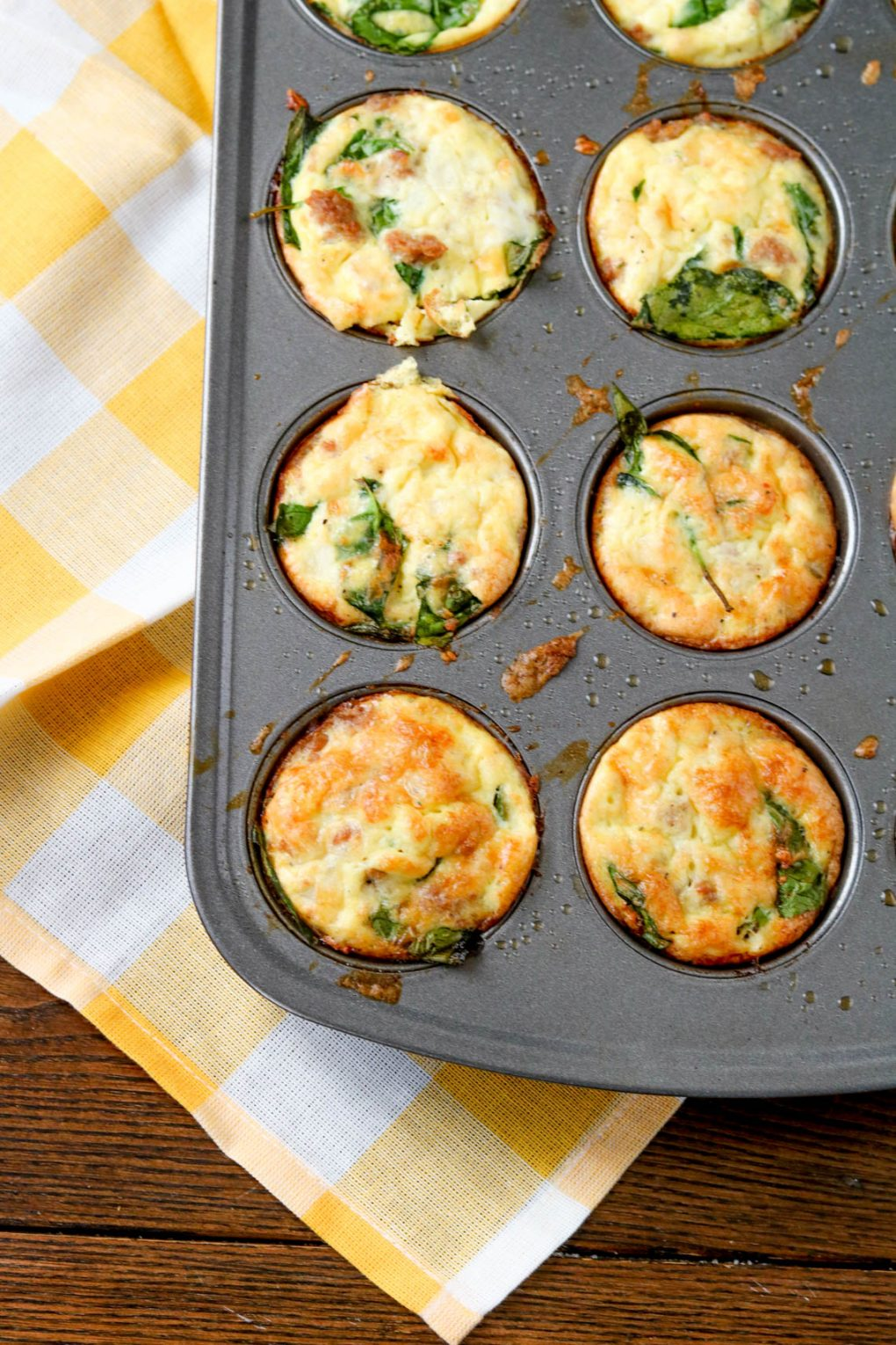 A muffin tin with spinach sausage egg muffins. The silver muffin tin is sitting on a wood table with a yellow and white checkered towel underneath.