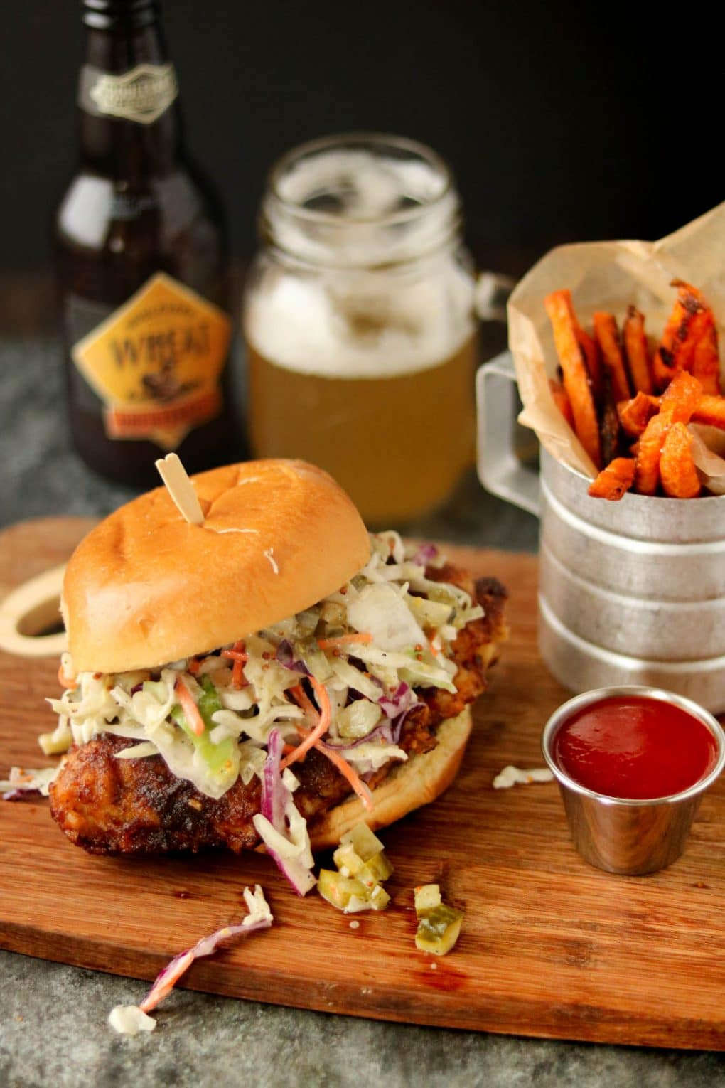 Nashville Hot Chicken Sandwich on a wooden cutting board. There's a serving of sweet potato fries sitting next to it, a small sauce cup of ketchup and a beer in the background