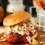 Nashville hot chicken sandwich sitting on a wooden cutting board