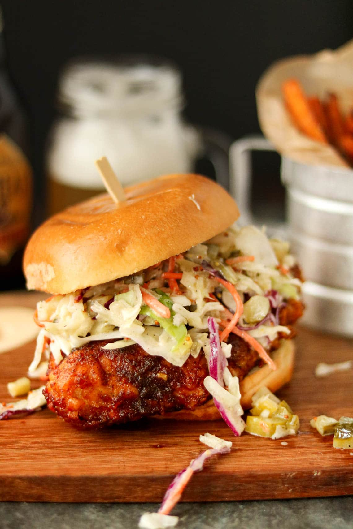 Nashville hot chicken sandwich sitting on a wooden cutting board