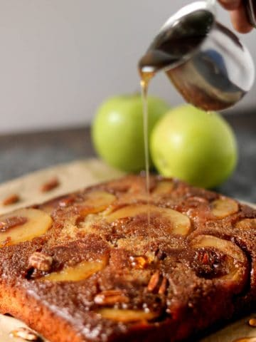 a person drizzling honey over an apple upside down cake