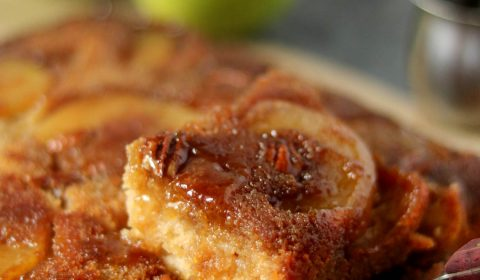 a slice of apple upside down cake being pulled up by a spatula