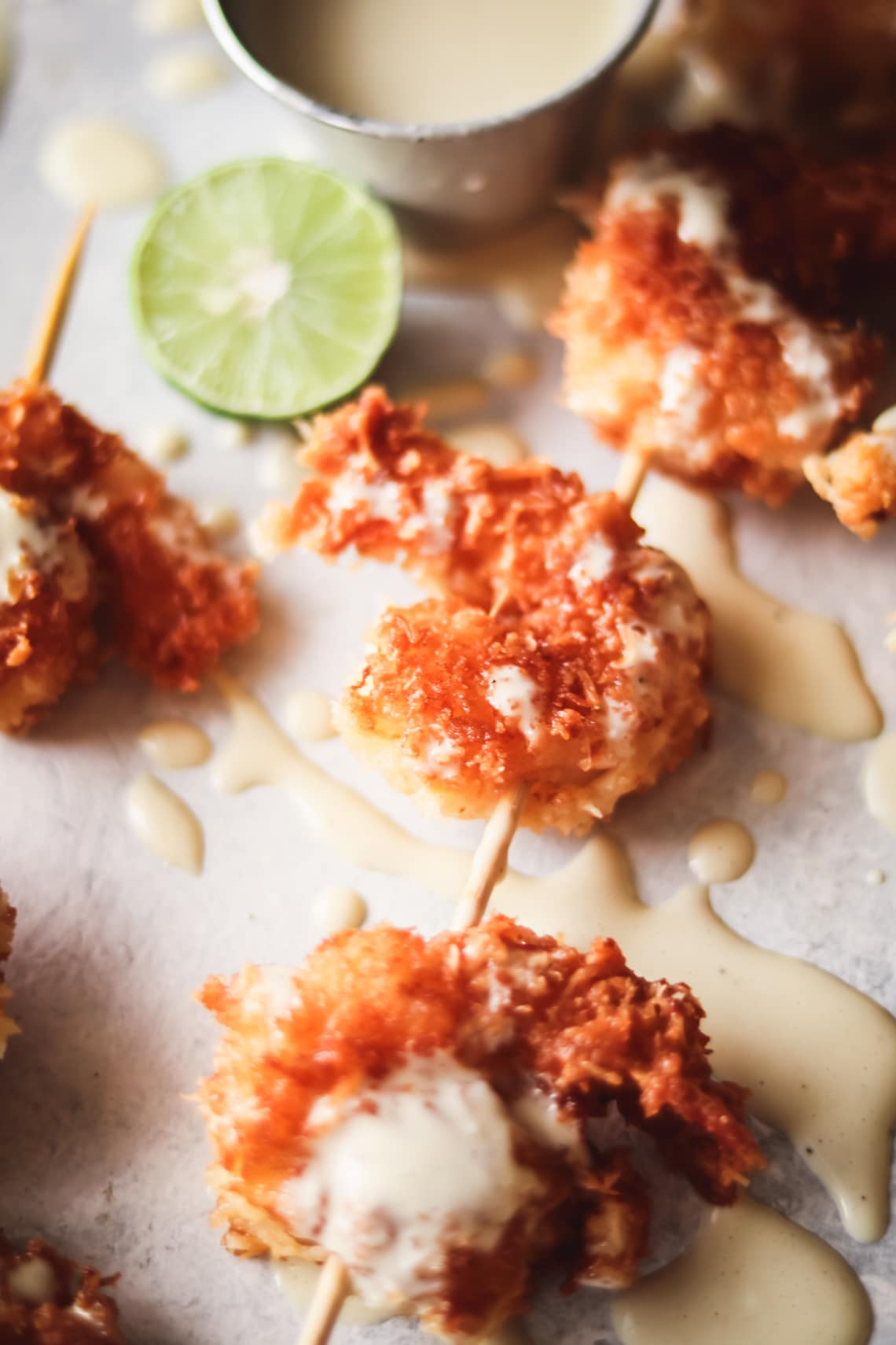 coconut shrimp on wooden skewers with key lime aioli drizzled all over. There are sliced key limes laying around the coconut shrimp on the table and a small sauce cup of the key lime aioli