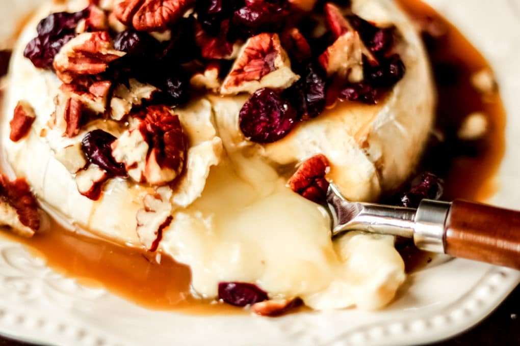 cranberry caramel baked brie with a spoon scooping out a serving