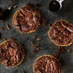 four pecan pie mini-tarts on a table