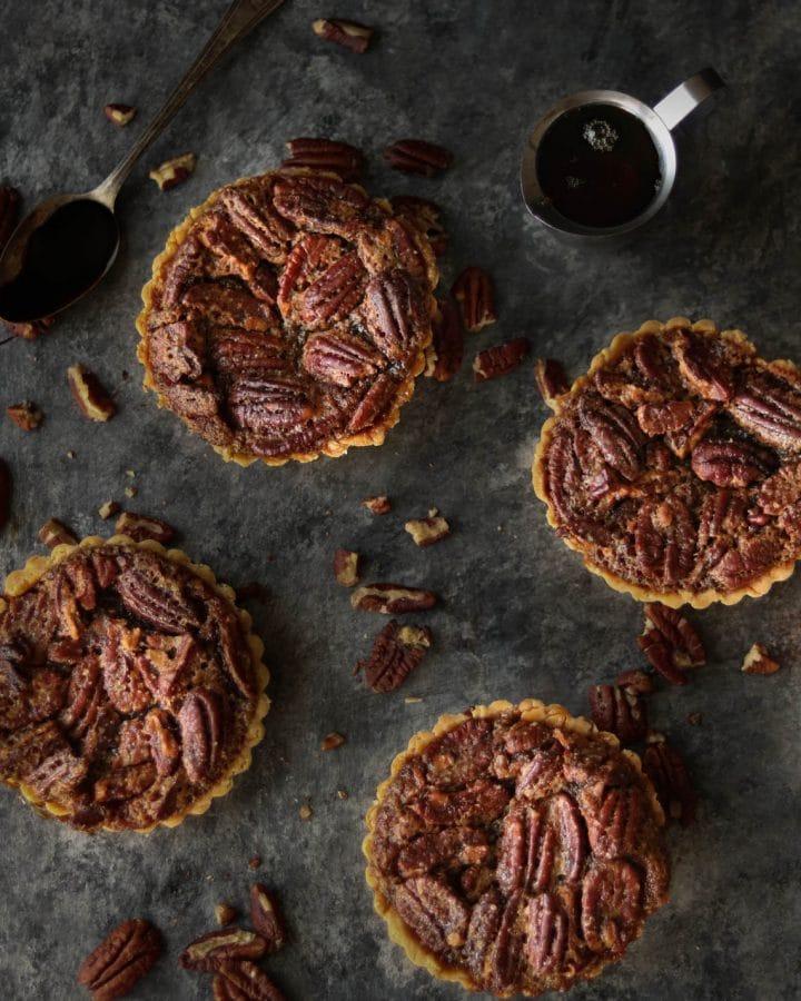 four pecan pie mini-tarts on a table