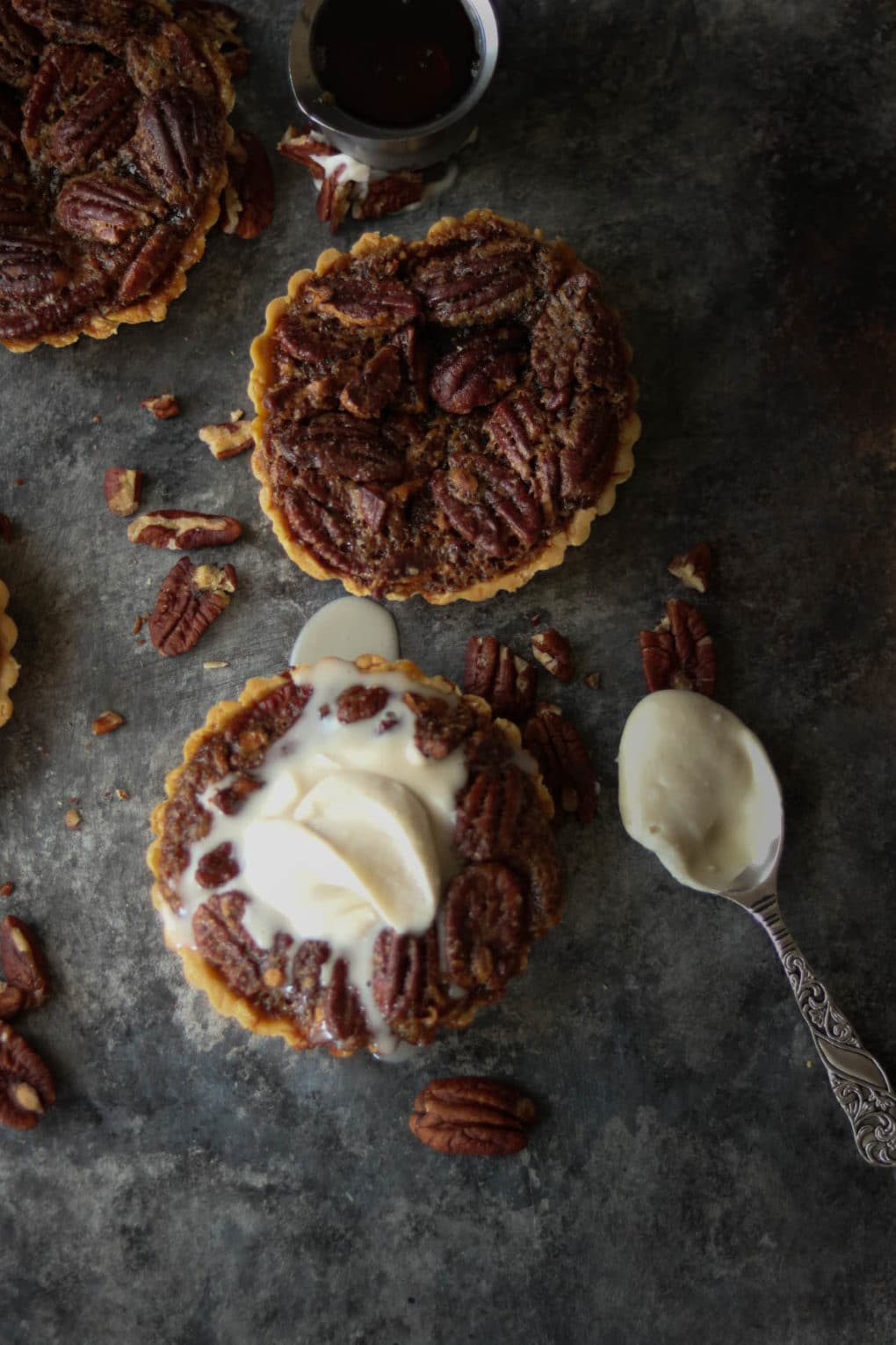 pecan pie mini-tarts, one with whipped cream on top and spoon laying nearby