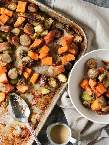pan-roasted vegetables and sauste on a sheet pan and served in a white bowl with maple tahini