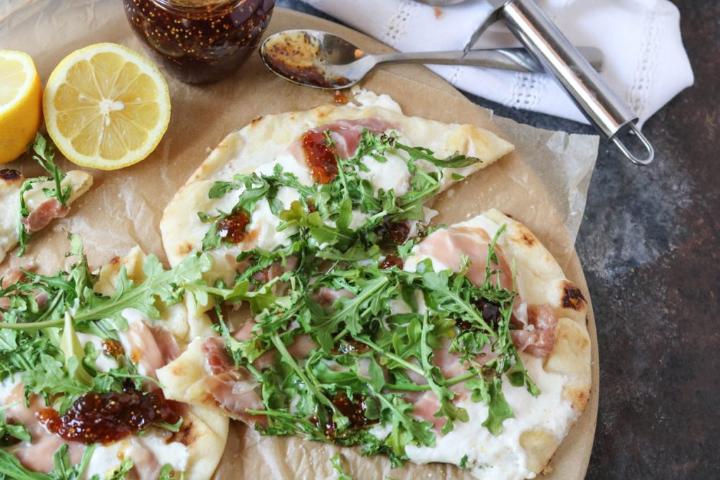 Prosciutto Burrata Pizza with Fig Jam on a table and sliced
