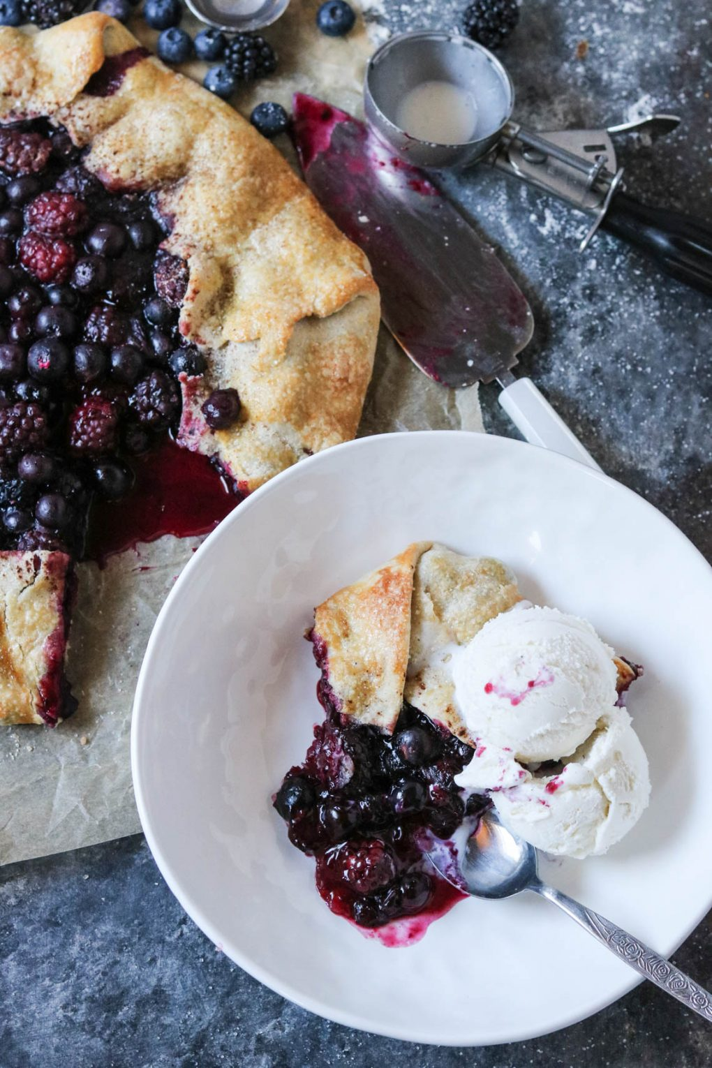 a slice of Rustic Berry Galette in a white bowl with vanilla ice cream on top