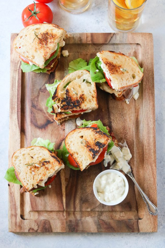 5 BLT club sandwiches on a cutting board with a glass of iced tea