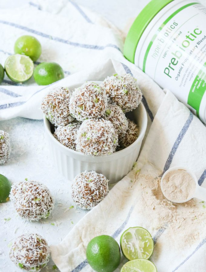 Key Lime Power Balls with Prebiotics sitting in a bowl next to a jar of Hyperbiotics Prebiotic powder and key lime wedges