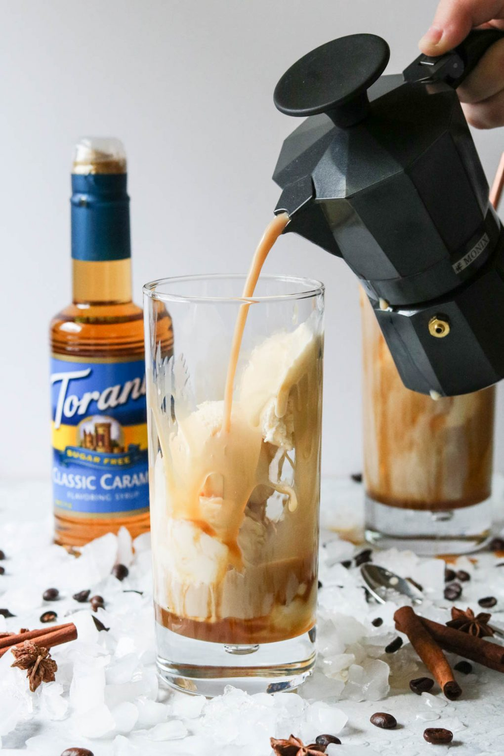 someone pouring coffee into a dirty chai ice cream float