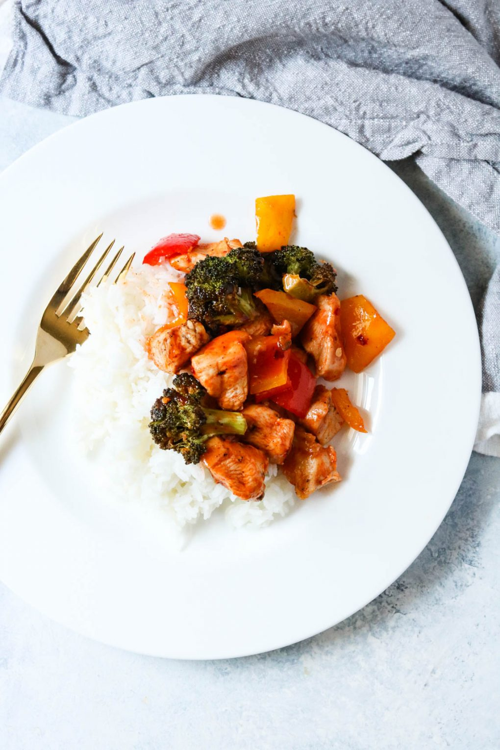 a serving of sheet pan sweet and spicy chicken served over white rice on a white plate