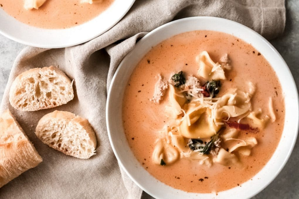 a bowl of creamy tomato tortellini soup with a sliced baguette sitting nearby