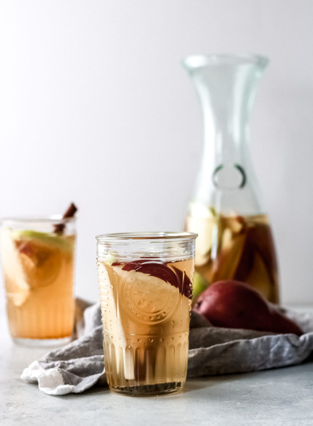 two glasses of apple cider sangria and a carafe