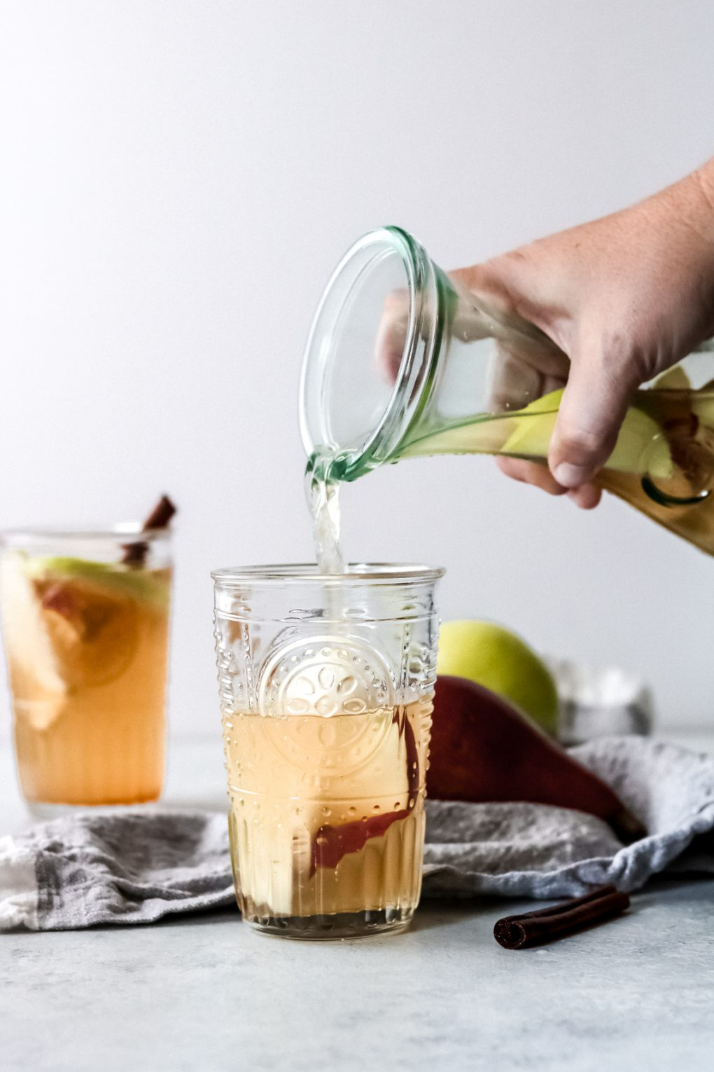 someone pouring apple cider sangria from a carafe into a glass