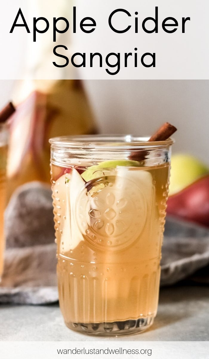 a glass of apple cider sangria with a carafe in the background