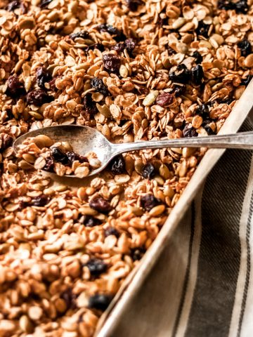 a sheet pan with homemade cinnamon and raisin granola with a spoon