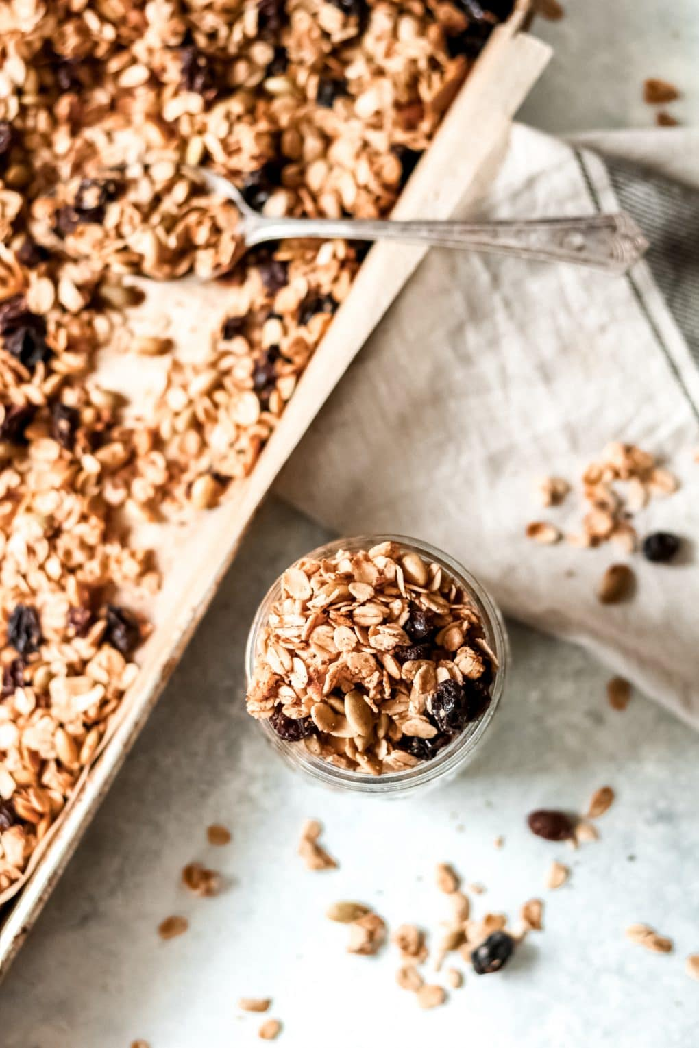 a pan of homemade cinnamon and raisin granola with a jar of granola sitting next to it