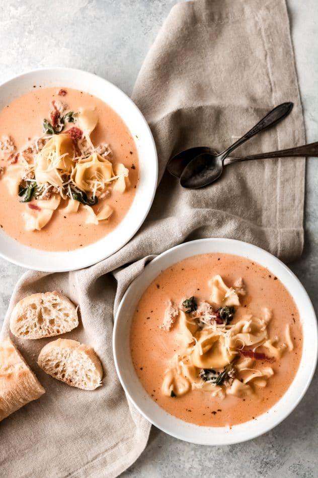 two bowls of creamy tomato tortellini soup